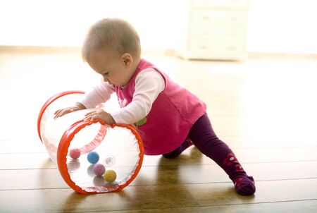 released: Baby girl (9 months) playing with soft toys at home. Toys are property released.