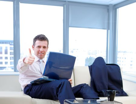 compute: Happy successful businessman sitting on couch at office, working on laptop compute, smiling and showing okay hand sign.