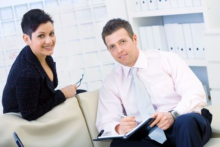 Smiling coworkers, businessman and businesswoman sitting on sofe and working together at office, doing paperwork. photo
