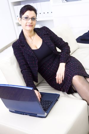Happy businesswoman sitting on sofa at office and working on laptop computer, looking at camera, smiling. photo