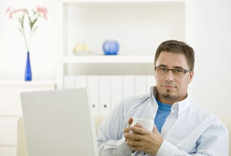 Happy casual man using laptop computer at home drinking coffee. Stock Photo - 3916159