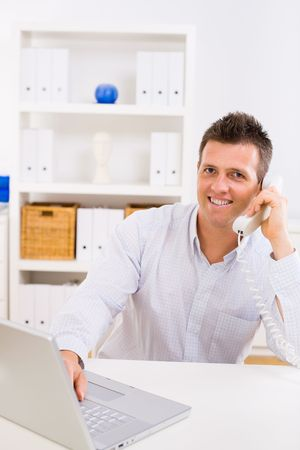 Business man working on computer at home calling on phone. Stock Photo - 3916163