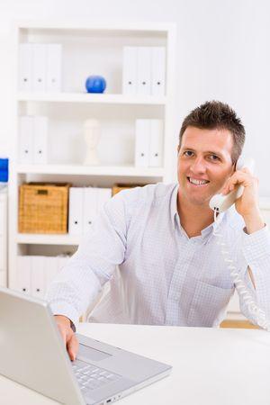 outwork: Hombre de negocios de trabajo en ordenador en casa llamando por tel�fono.