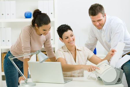 Team of happy office people working at office using fax.  photo