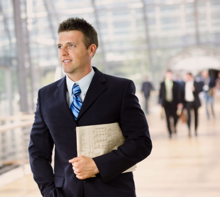 Portrait of happy successful businessman holding newspaper, smiling. Stock Photo - 3916194