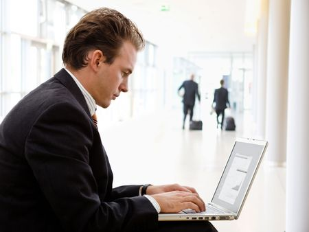 Businessman working on laptop computer at office lobby. photo
