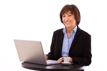 Senior businesswoman working on laptop computer at coffee table. photo