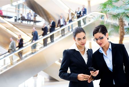 mobilephones: Two young businesswomen sharing text message on mobile phone in lobby, with businessmen traveling on escalator in background.