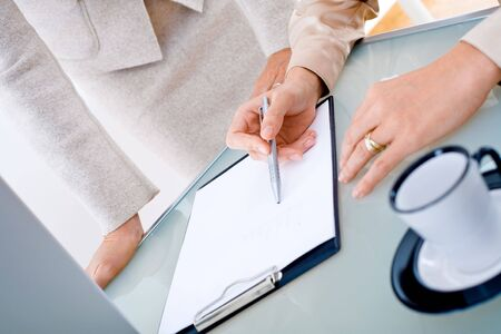 image consultant: Close-up of female hands working with documents on table. Stock Photo