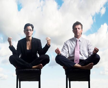 Businessman and businesswoman meditate in front of the open blue sky. photo
