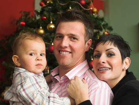 A family of three are very happy in front of a Christmas Tree. photo