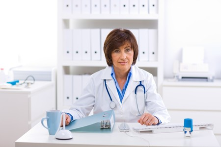 offiice: Senior female doctor sitting at desk working at offiice. Stock Photo