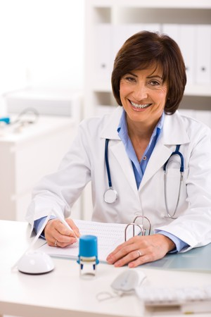 Senior female doctor working at desk, smiling. photo