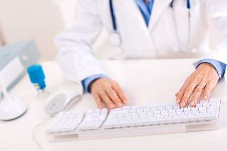 doctora: Closeup de manos de las mujeres m�dico escribiendo sobre teclado de computadora. Foto de archivo