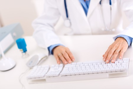 image consultant: Closeup of hands of female doctor typing on computer keyboard.