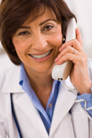 general knowledge: Senior female doctor calling on phone, smiling.