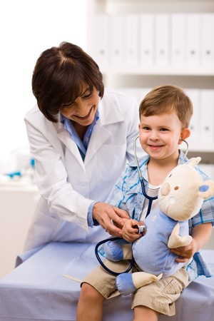 doctor toys: Senior female doctor examining happy child, smiling.