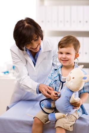 doctora: Superior de mujeres m�dico examinar ni�o feliz, sonriente. Foto de archivo