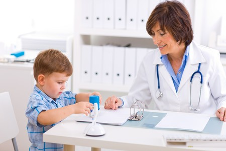 medications: Senior female  pediatrician playing with child at doctors office.