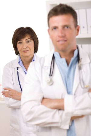 Portrait of medical doctors male and female at office. Focus on woman. photo