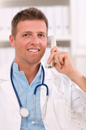 Medical doctor talking on phone at office. photo
