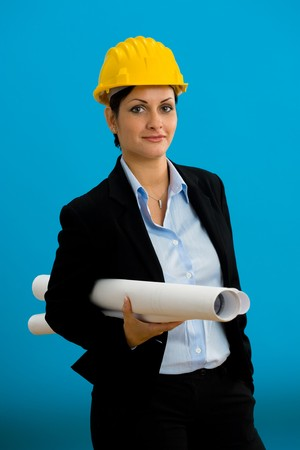 Young female architect in hardhat with blueprint isolated on blue. photo