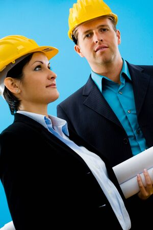 Young architects in yellow hardhat against blue background. photo