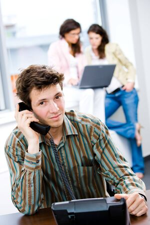 Young happy customer service worker receiving phone calls at office, smiling. photo