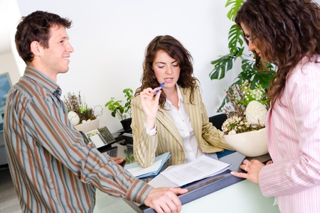 Casual business team working together at office reception, looking at documents, talking. Stock Photo - 4089878