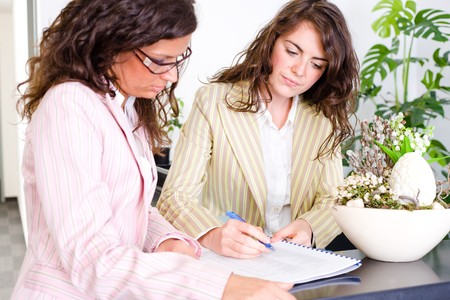 Casual businesswomen working together in team at office reception, looking at documents, talking. Stock Photo - 4089880