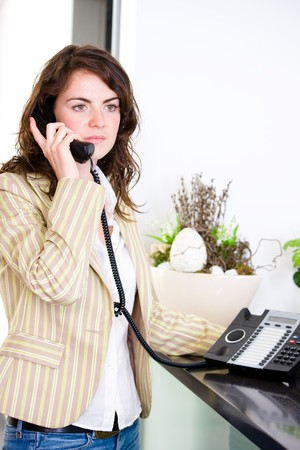 Young female receptionist receiving phone calls at office reception. photo