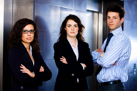 Portrait of successful happy business team posing at office lobby in front of elevator. Dark background. photo