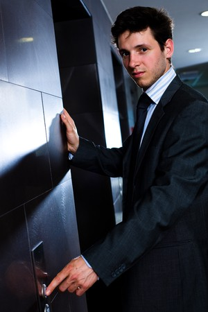 businessman waiting call: Young businessman standing at office in front of elevator.