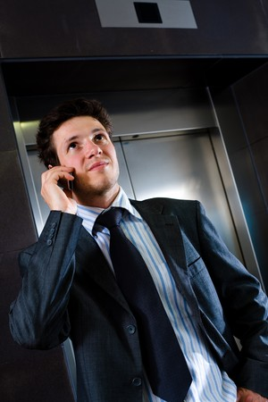 Young businessman standing at office lobby waiting for elevator and calling on mobile phone. photo