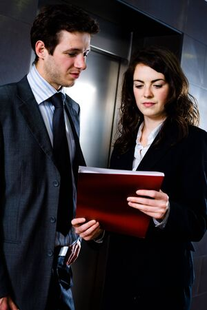 Young businesspeople working together at office corridor, looking at red document folder, reading reports. Stock Photo - 4089889