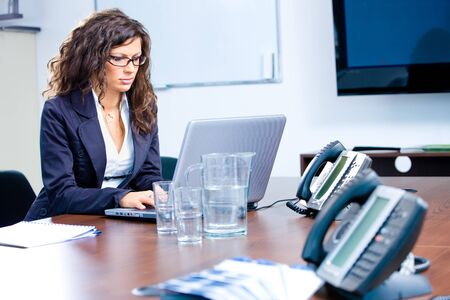 Young businesswoman working on laptop computer at office in meeting room. Stock Photo