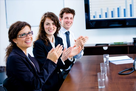 Happy businesspeople clapping on a training at office, smiling.