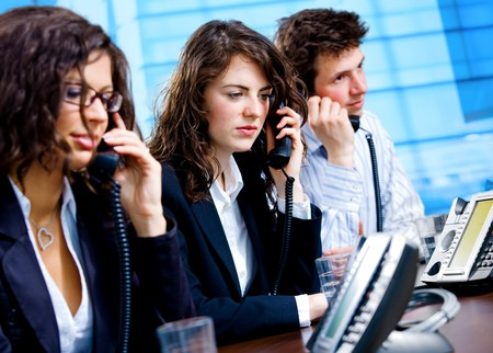 Young customer service operators sitting in a row at table and calling on landline phone, smiling. Stock Photo - 4105338