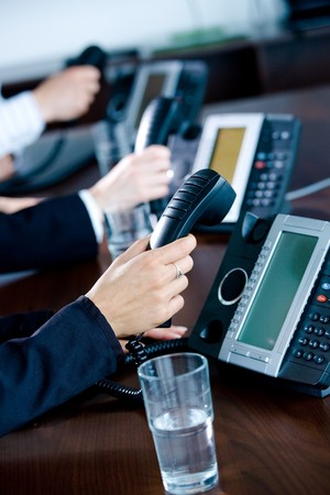 telework: Close-up of hands holding landline phone recievers at customer service office.