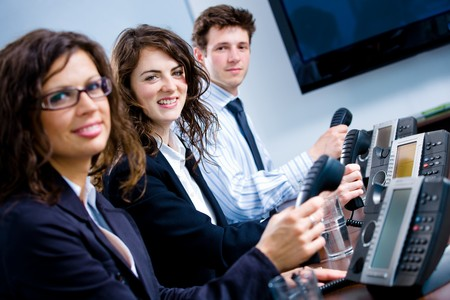 Young happy customer service operators sitting in a row, holding phone receiver, looking at camera, smiling. Stock Photo - 4089846