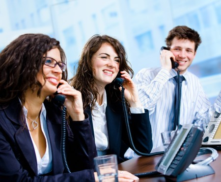 Happy team of customer service operators calling on phone.