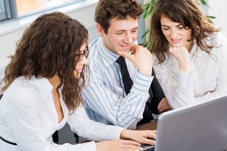 Happy team of young business people sitting in meeting room, working together on laptop computer, smiling. Overhead view. Stock Photo - 4089885