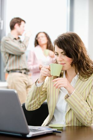 Team of young successful businesspeople talking and drinking coffee at office, businesswoman working on laptop computer in front.  photo