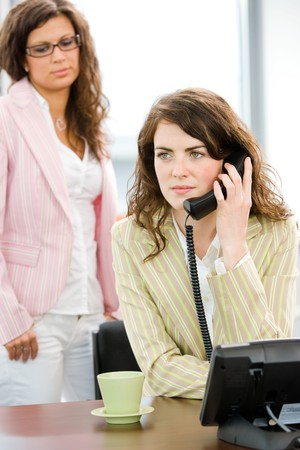 Young female office workers - businesswoman receiving phone calls. photo