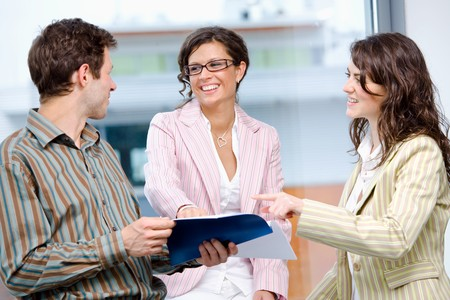 Happy young businesspeople having meeting at office and reading documents, smiling. Stock Photo - 4089873