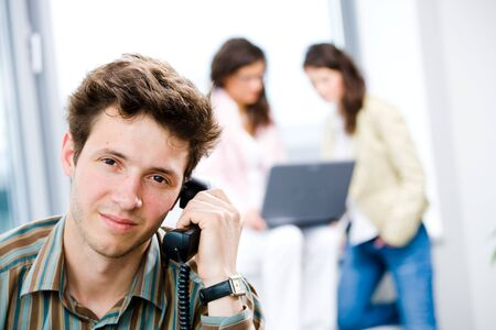Young businessman receiving phone calls at office while business people team working in background.  photo