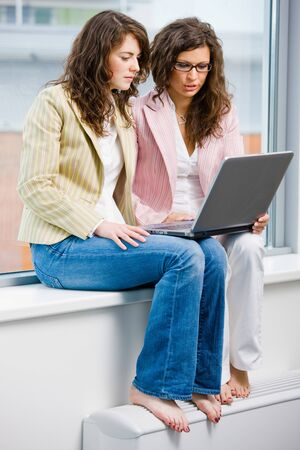 Young creative businesswomen team working on laptop computer at office. photo