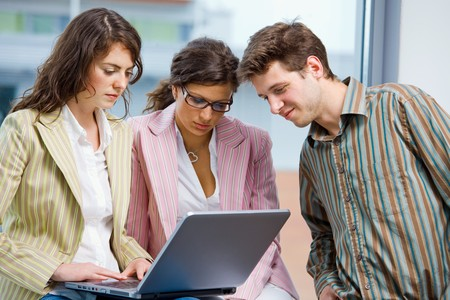 Young businesspeople having meeting at office, working in team together on laptop computer. Stock Photo - 4089908