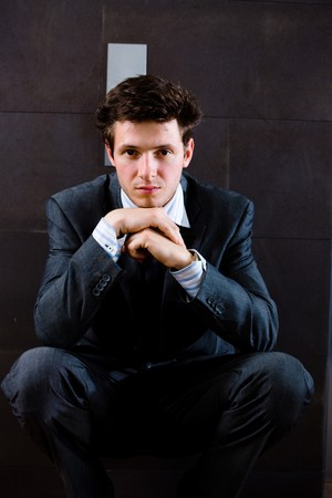 squat: Young businessman squat on office corridor and thinking, looking at camera, daydreaming. Stock Photo