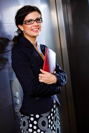 Young happy businesswoman holding red folder and posing for portrait on office corridor, smiling. photo